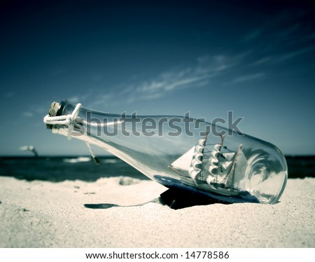 Stock Photo Bottle with ship inside lying on the beach. Conceptual image