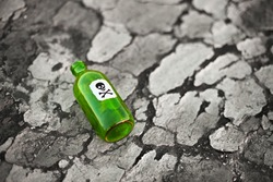 Bottle with the poison lying on poisoned ground
