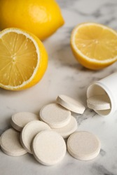 Bottle with vitamin pills and lemons on white marble table, closeup
