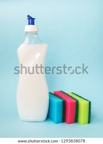 Bottle with white dishwashing liquid and three foam sponges of different colours on a blue background. Kitchen detergent. Household chemicals. Household chores. #1293838078