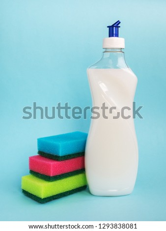 Bottle with white dishwashing liquid and three foam sponges of different colours on a blue background. Kitchen detergent. Household chemicals. Household chores. #1293838081