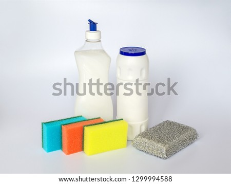 Bottle with white dishwashing liquid, scouring powder and four foam sponges of different colours on a white  background. Kitchen detergent. Household chemicals. Household chores. #1299994588