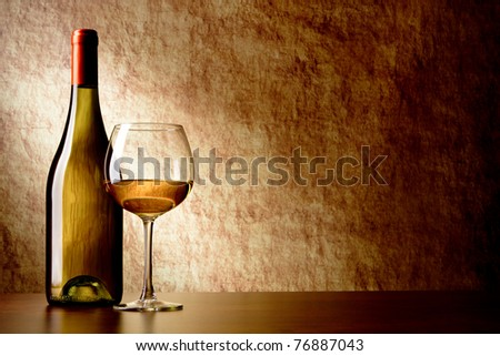 bottle with white wine and glass on a old stone. bottle in the foreground