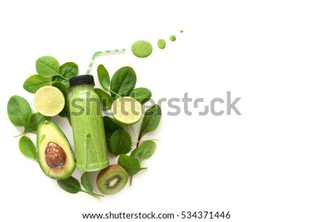 Bottled detox drink surrounded by green foods including spinach and kiwi  #534371446