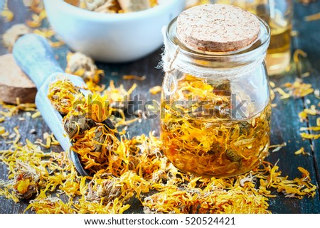 Bottles and dried calendula officinalis petals with macerated oil on wooden background. Selective focus
