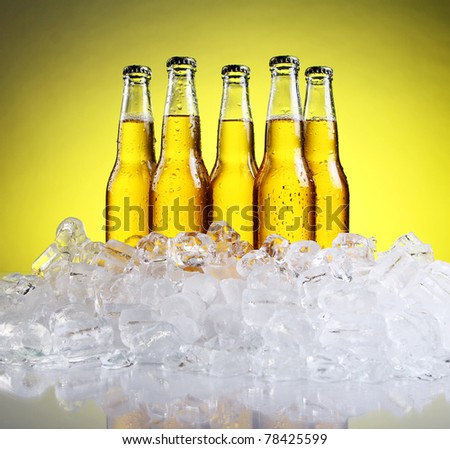 Bottles and Glass of beer with foam over yellow background