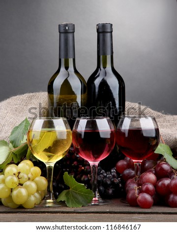 bottles and glasses of wine and grapes on grey background