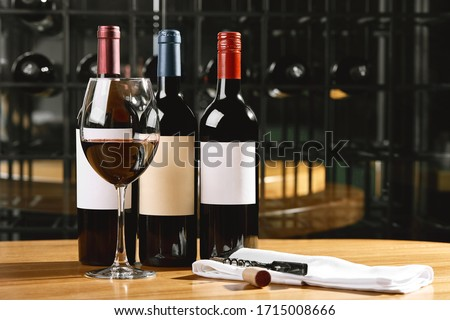 Bottles and glasses with wine on the table. Wine drinking culture concept. Apperetes and survivors. Copy space, dark background Stock photo ©