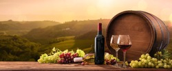 Bottles And Wineglasses With Grapes And Barrel On A Sunny Background. Italy Tuscany
