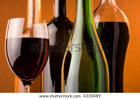 bottles from white, red and sparkling wine and glass of red wine