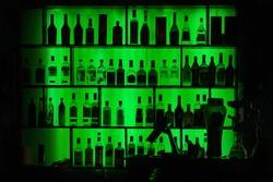 Bottles of alcohol and spirits at bar or pub shelves with green backlit. Bar background.
