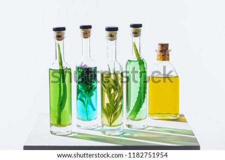 bottles of aromatic essential green and yellow oils with herbs on white cube #1182751954