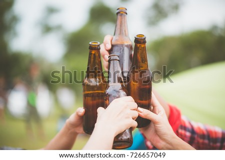 Bottles of beer.Group of friends enjoying party.people are drinking beer and laughing . The guy plays the guitar. Everyone has a great mood. Summer time. Vintage effect style pictures.