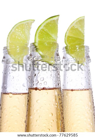 bottles of beer with lime on white background