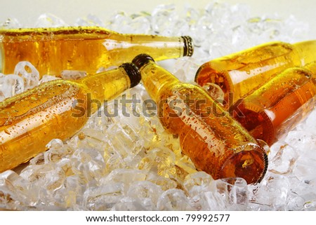 Bottles of cold beer lying in the ice. Close view.