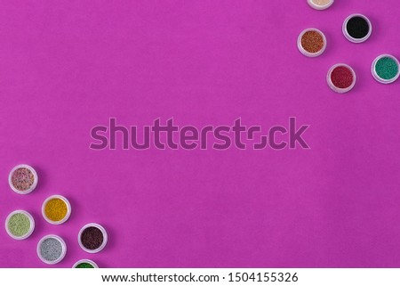 Bottles of Colorful glitters, color changing shining powder. Manicure decoration glitter pigment set. Flat lay. Top view sequins for nails and makeup. Sparkles in jar. purple background copy space.