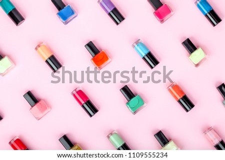 bottles of colorful nail polish on pink background. beauty and fashion trendy concept. flat lay, top view #1109555234