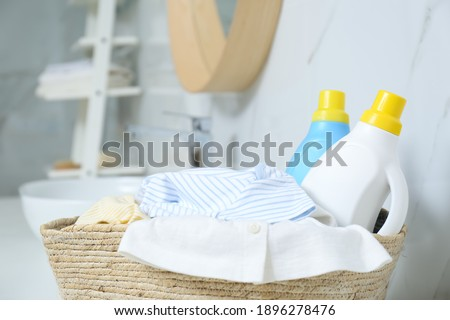 Bottles of detergent and children's clothes in wicker basket indoors, closeup Foto stock ©