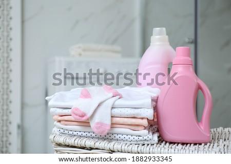 Bottles of detergent and children's clothes on wicker basket in bathroom Foto stock ©