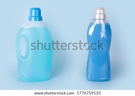 Bottles of detergent and fabric softener on blue background. Containers of cleaning products, household chemicals. Liquid laundry detergent and conditioner. Laundry day, washing and cleaning concept. Foto stock ©