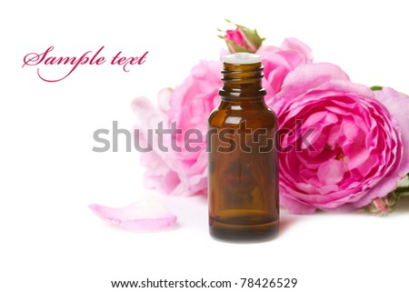 Bottles of essential oil and pink rose isolated over white
