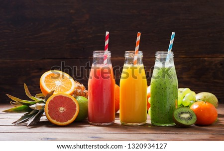 bottles of fruit juice and smoothie with fresh fruits on wooden table #1320934127