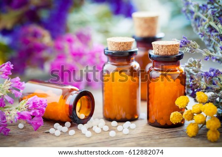 Bottles of homeopathic globules and healing herbs and flowers. Homeopathy medicine. Stock photo ©