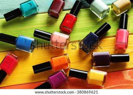 Bottles of nail polish on a colorful wooden table