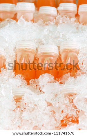 bottles of natural orange juice in the middle of ice