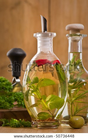Bottles of olive oil with mezzaluna and chopping board with herbs in background