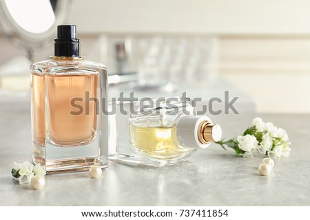 Bottles of perfume, flowers and pearls on table