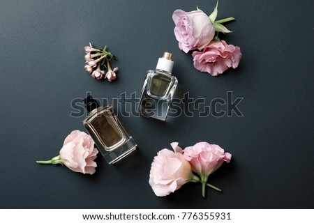 Bottles of perfume with flowers on dark background #776355931