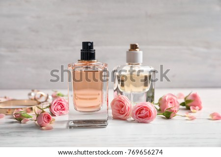 Bottles of perfume with flowers on light background