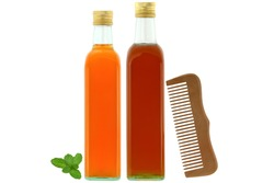 Bottles of raw and unfiltered organic apple cider vinegar with mother enzymes, organic honey next to wooden comb, ingredients for dry and damaged hair treatment isolated on white background