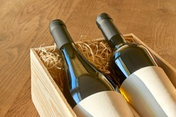 Bottles of red and white wine in wooden gift box with straw. Glass bottles with blank labels for use as mockup or template. Christmas, appreciation or celebration concept with copy space.