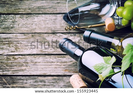 Bottles of red and white wine on wooden table