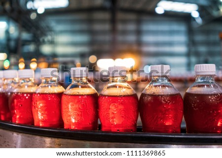 Bottles of red soda in the factory line. #1111369865