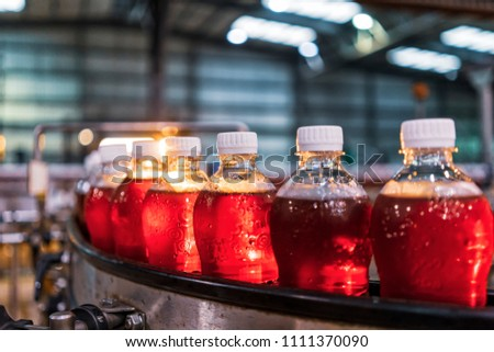 Bottles of red soda in the factory line. #1111370090