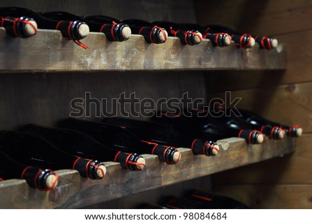 Bottles of red wine in rows in wine cellar