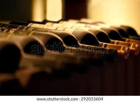 Bottles of red wine on a wooden shelf