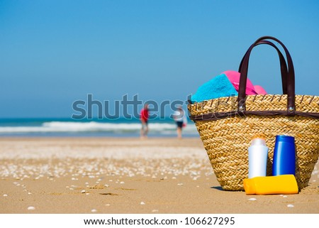 Bottles of sun screen in a basket. A happy older couple in the blurred background