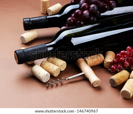 Bottles of wine, grapes and corks on brown background
