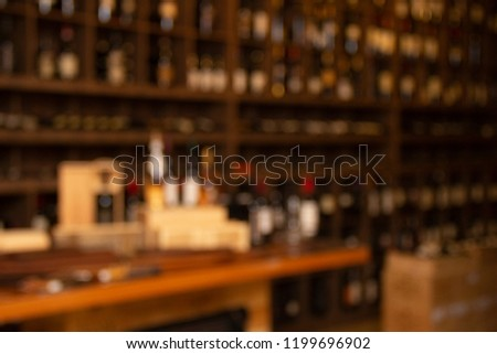 Bottles of wine on wooden shelves in winery collection #1199696902