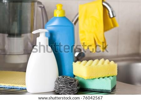 Bottles, sponges on foreground on kitchen