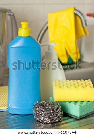 Bottles, sponges on foreground on kitchen