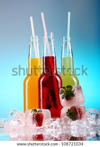 Bottles with colorful cocktails over blue background