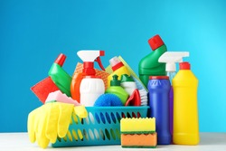 Bottles with detergent and cleaning tools on blue background