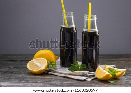Bottles with detox activated charcoal black lemonade on table. Healthy lifestyle drink. Natural hangover cure.