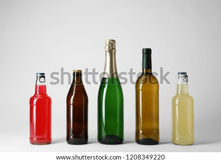 Bottles with different alcoholic drinks on light background #1208349220