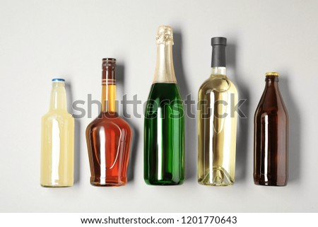 Bottles with different alcoholic drinks on light background, top view #1201770643